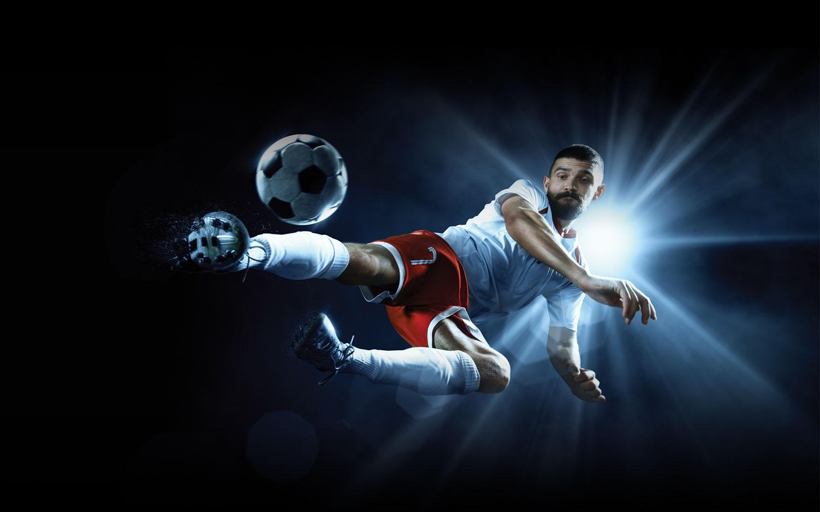 Professional footballer kicking a football