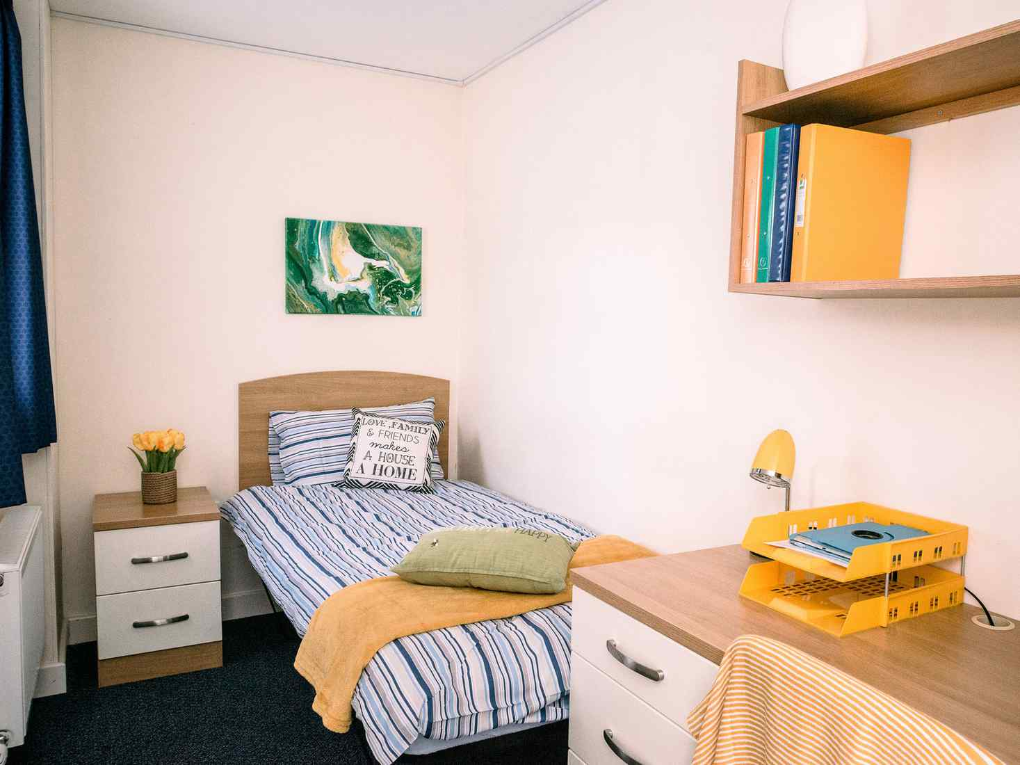 View of Garden Street room, with a single bed, drawers, desk and shelving.