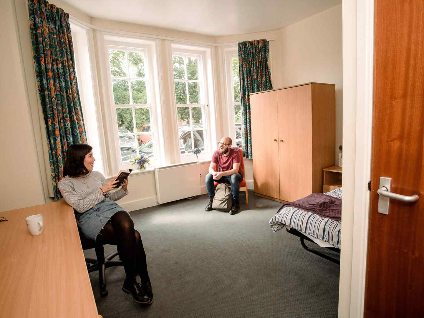 Two students sitting and chatting in a large ensuite room at City Residence. A large bay window is on the far wall, with a desk and wardrobe visible on either side.
