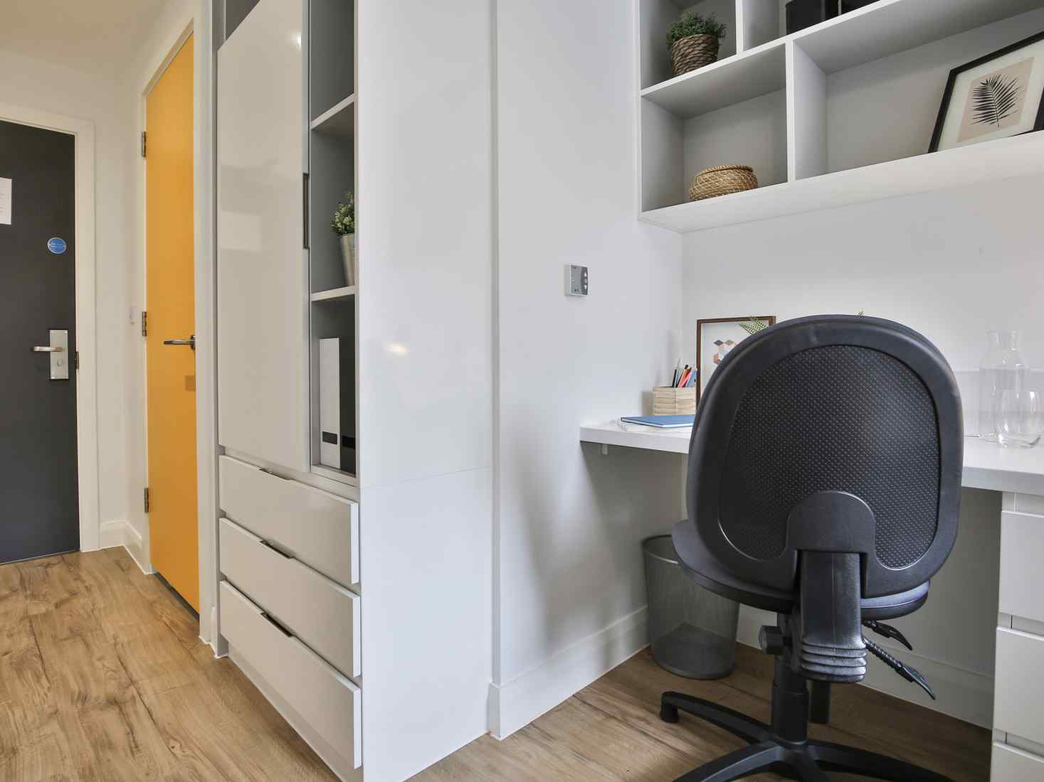 View of a Brickworks silver ensuite room, with desk, wardrobe and ensuite bathroom.