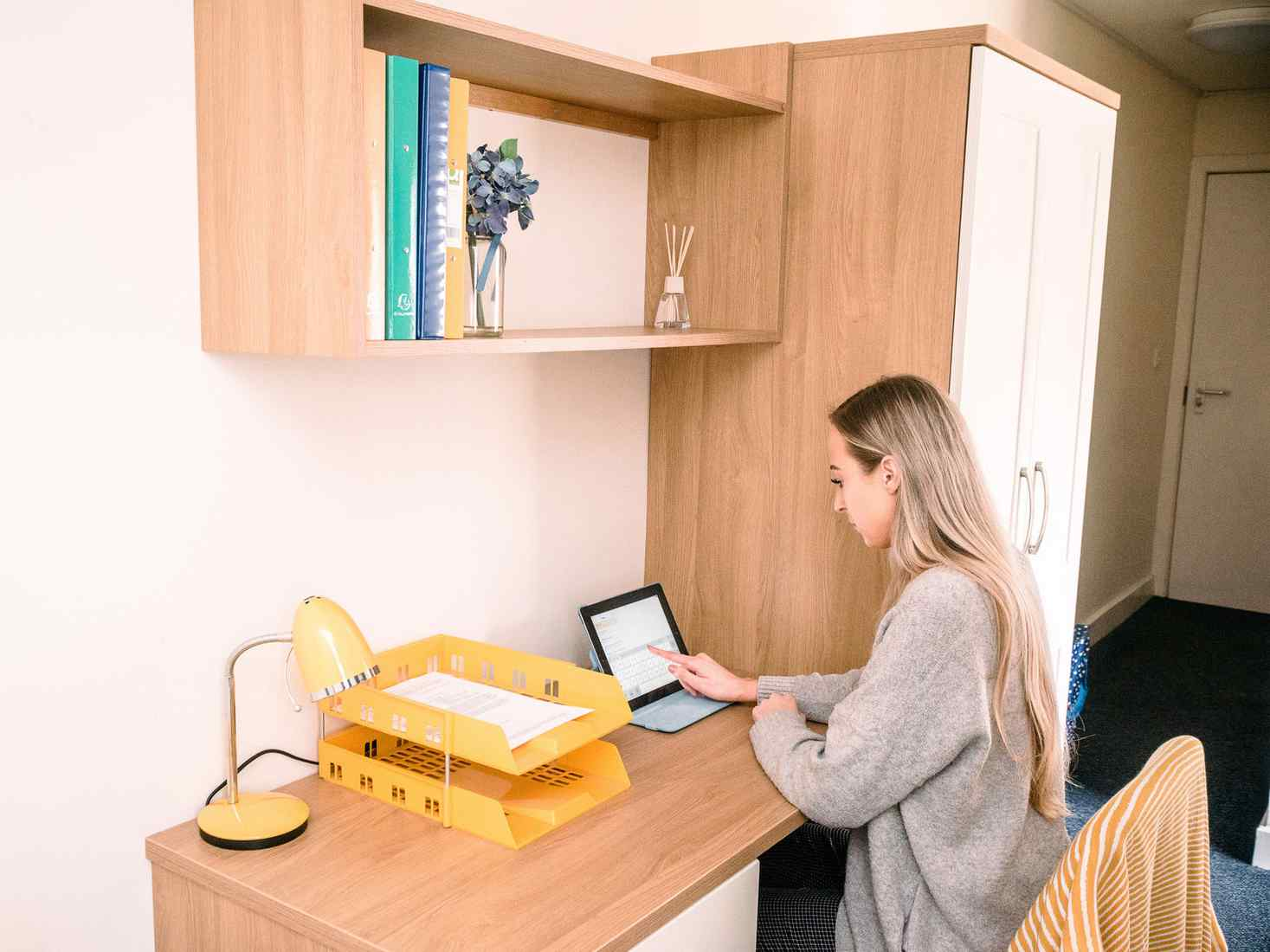 A student sits at a desk in a Garden Street standard ensuite room. There is a wardrobe next to the desk and shelving above.
