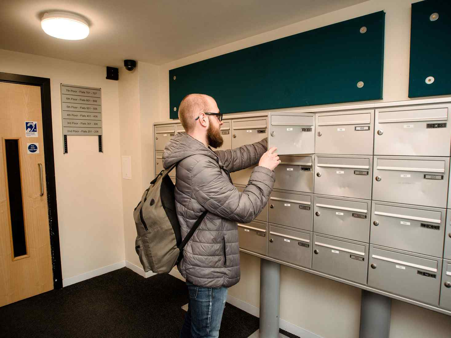 A student collects post from a postbox in the St John Central accommodation entrance area.