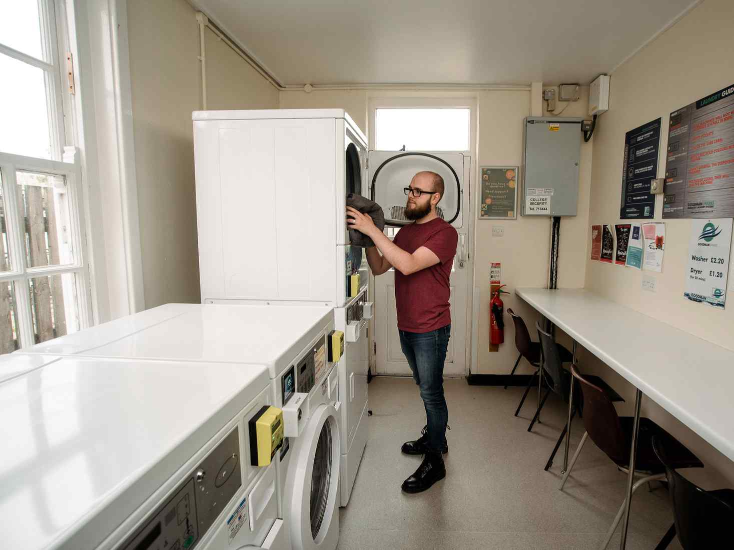 A student uses one of the washing machines in a laundry room at City Residence accommodation site.