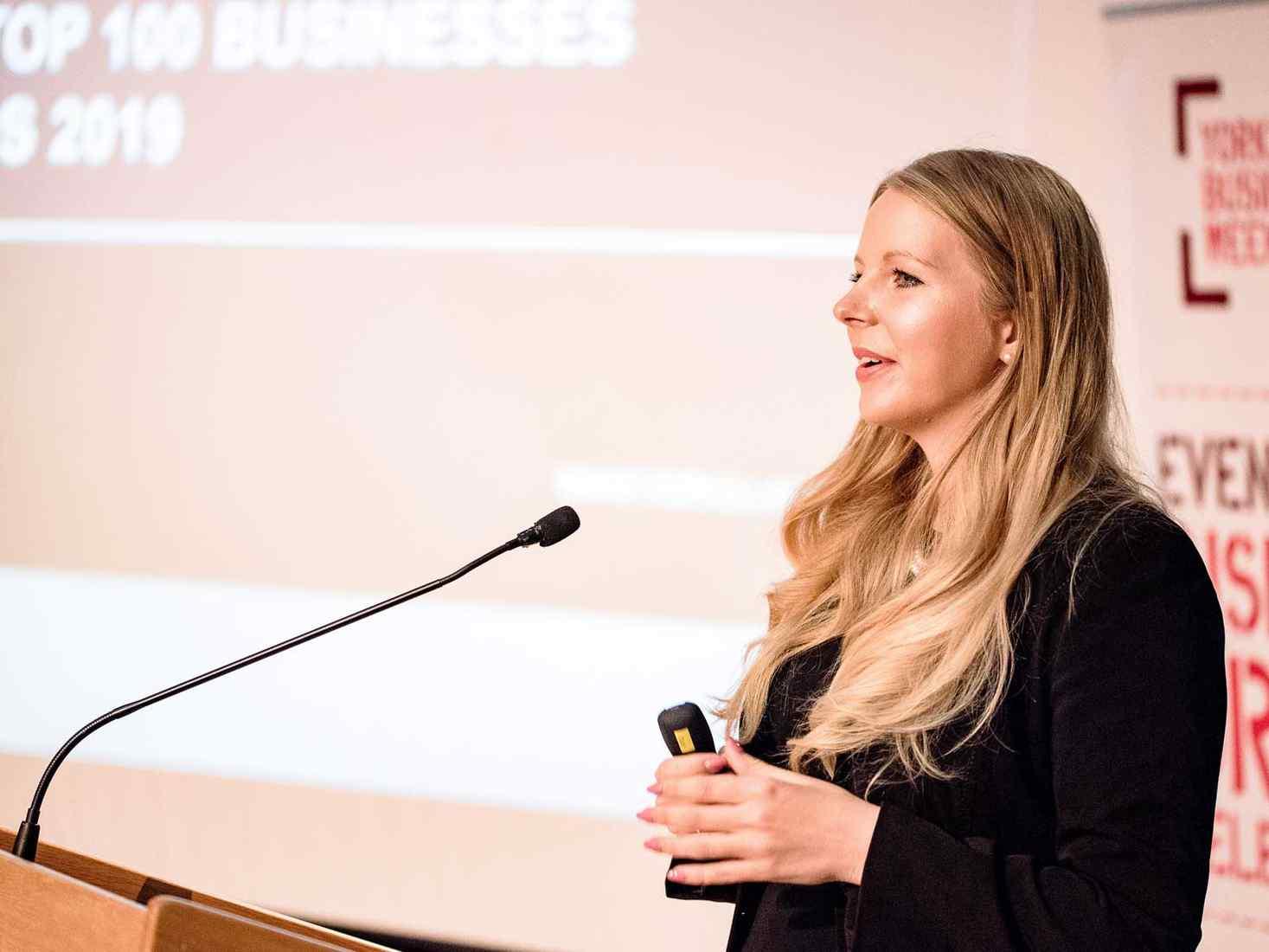 Lecturer Rebecca Biggins stands at a podium presenting at the Top 100 event 2019.