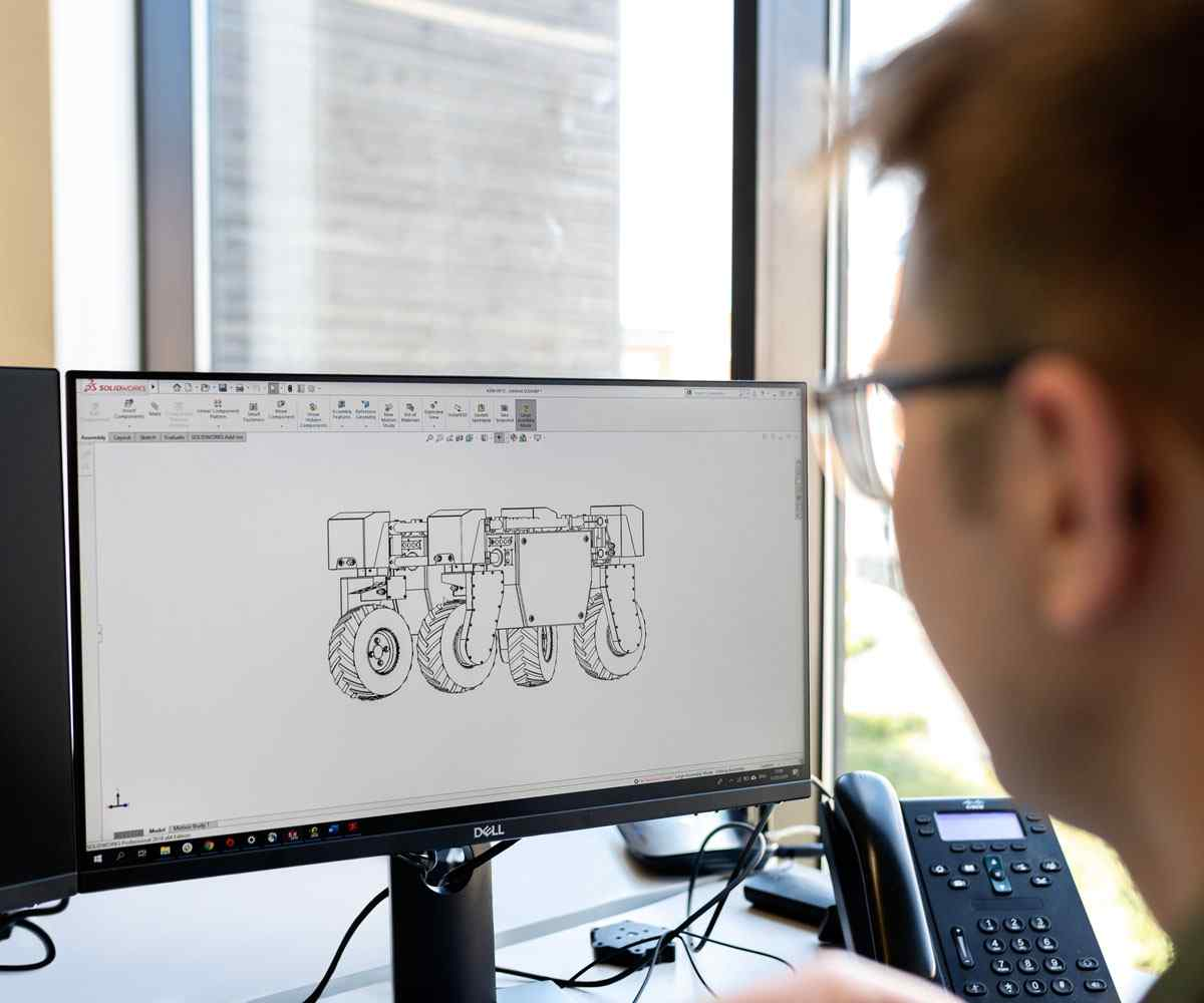 A man looking at an engineering design on a computer screen