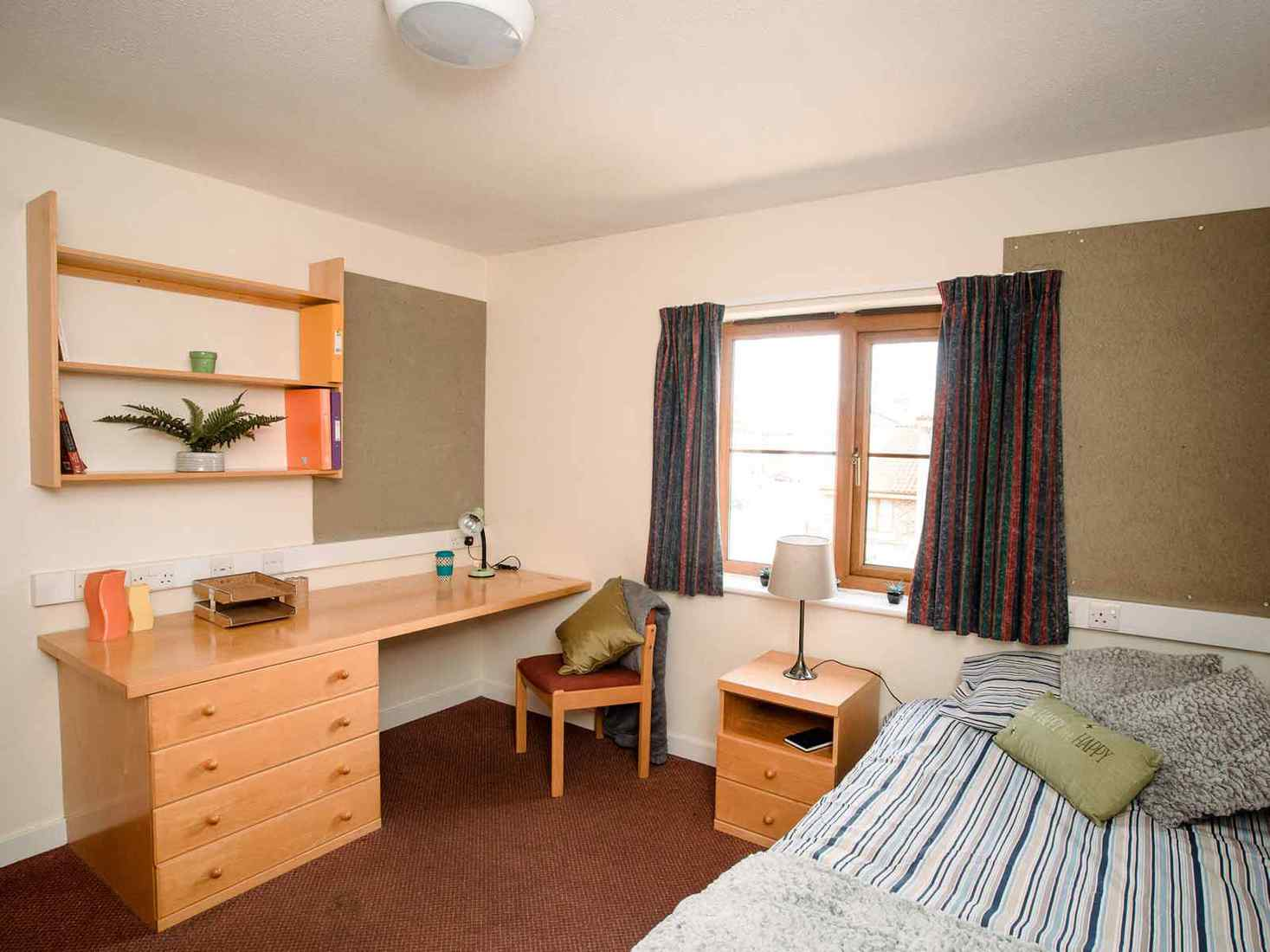 Student bedroom in Limes Court with bed, desk, side table, shelves and noticeboard