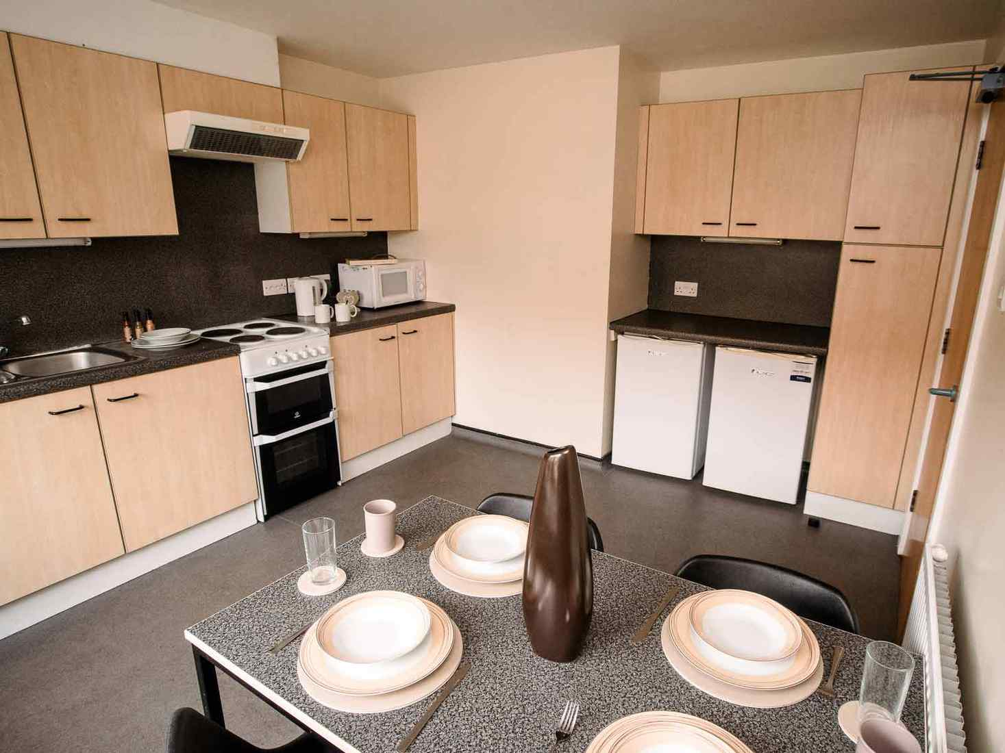 View of a kitchen in Limes Court, with cupboards on two walls, an oven, fridges, microwave, and table set for four.