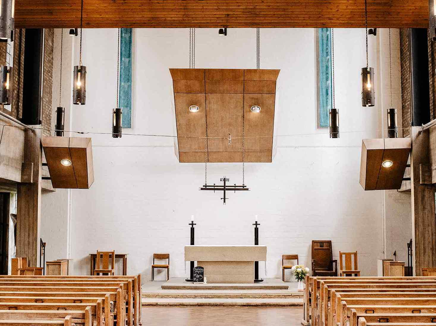 Inside Chapel, looking down aisle towards altar with wooden benches on both sides