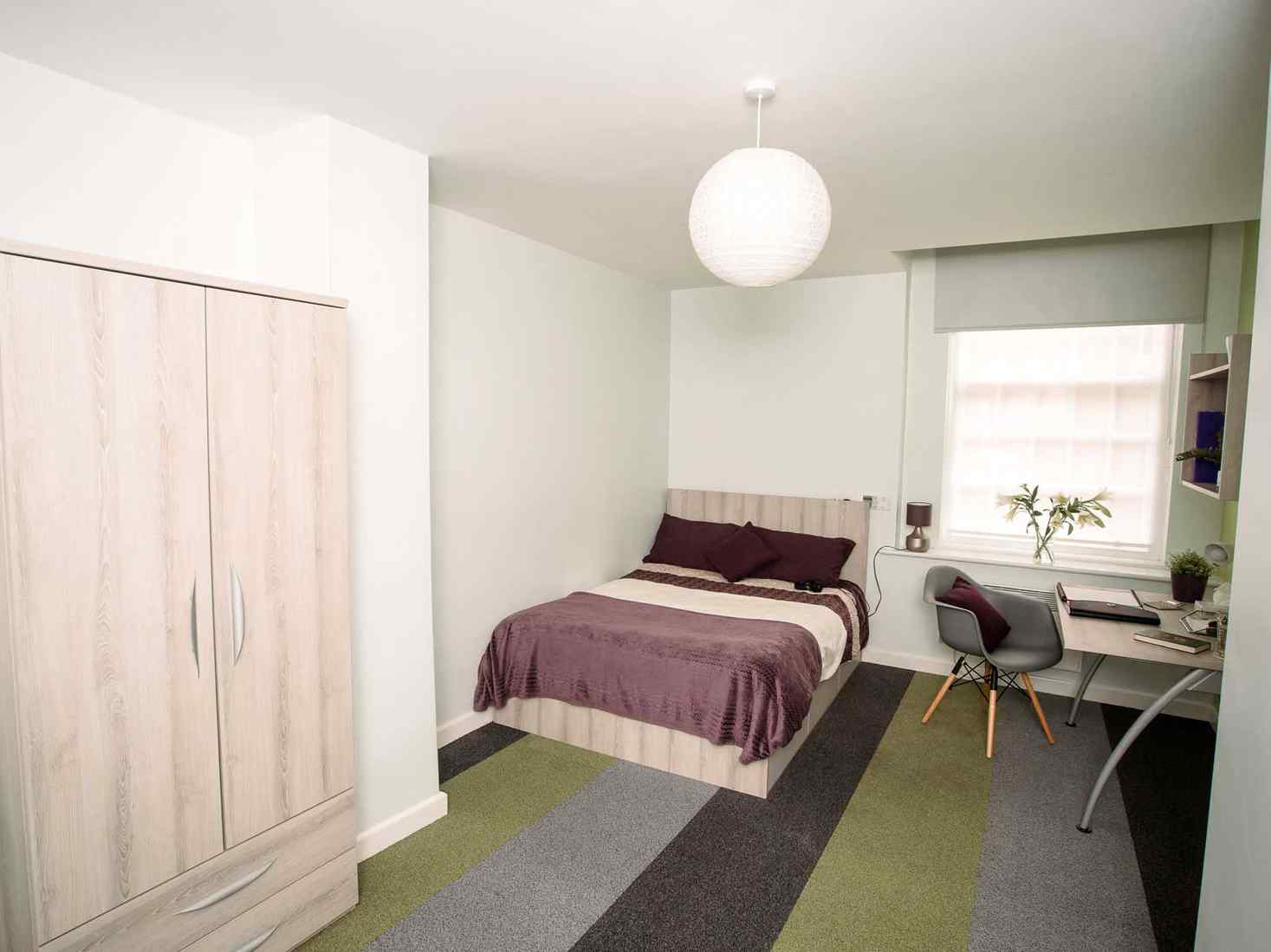 Student room with double bed, wardrobe and desk