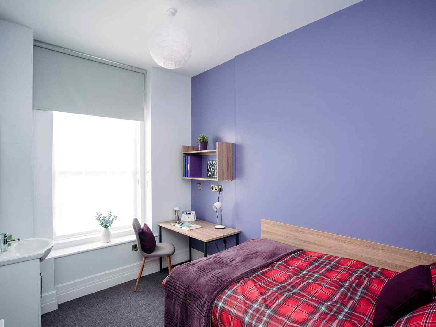 Student bedroom with double bed, desk and sink