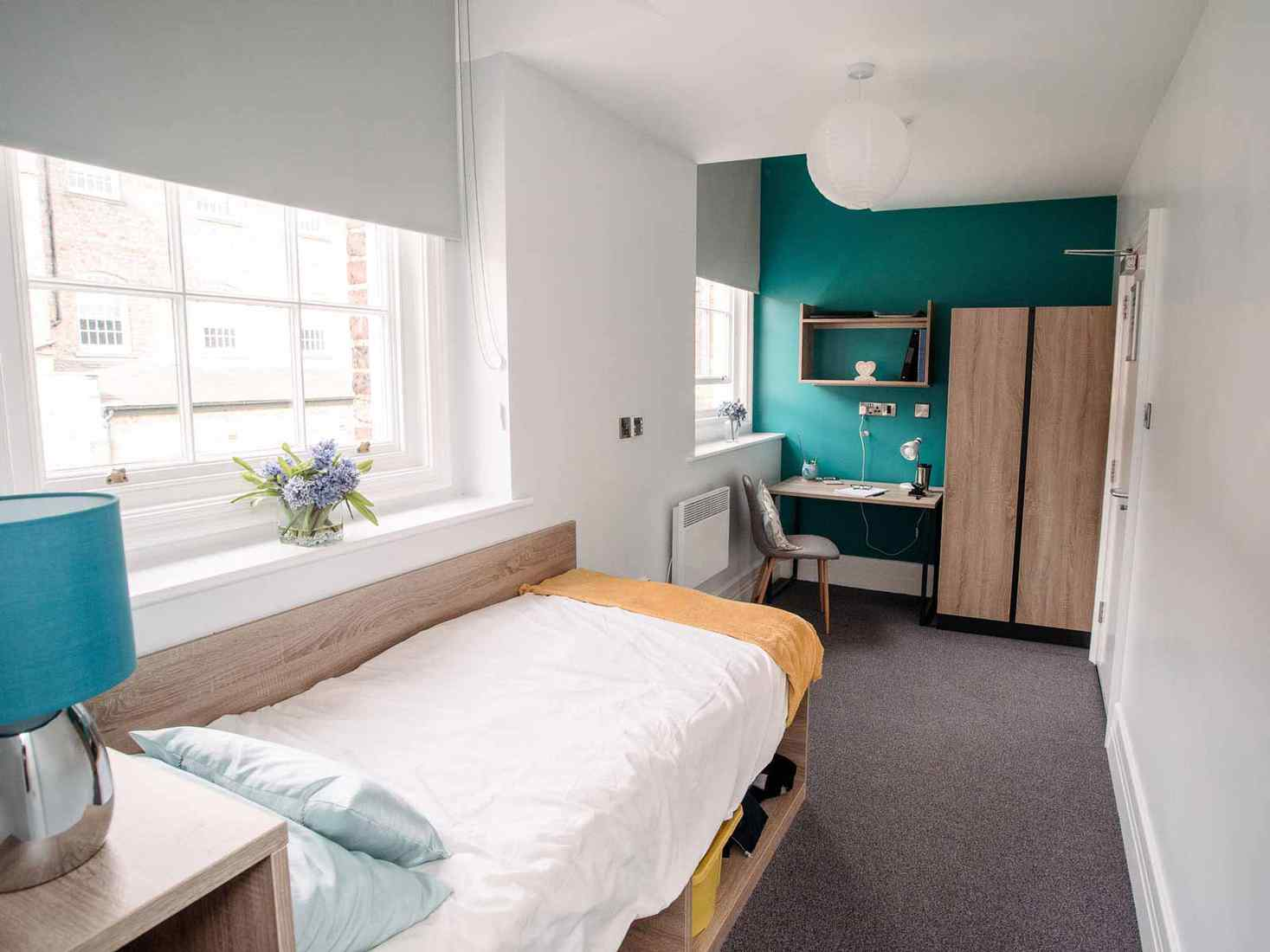 Student room with single bed, desk and wardrobe