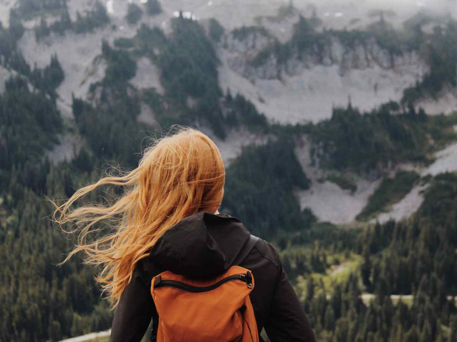 Girl with backpack facing towards mountain