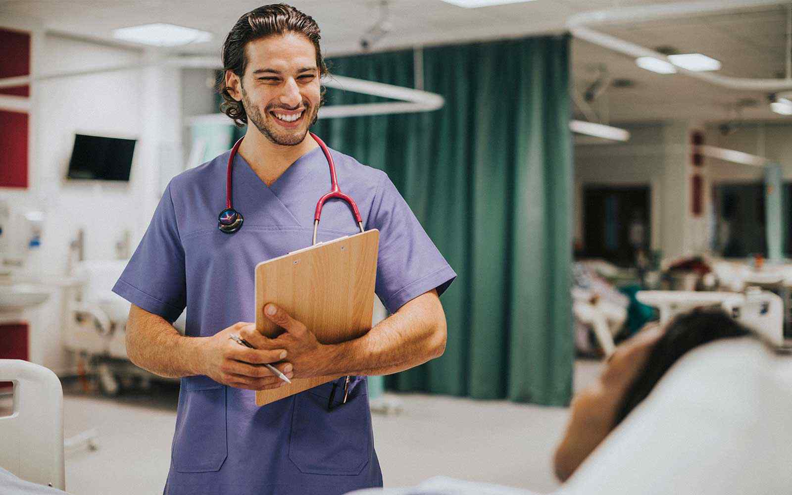 A student nurse in blue scrubs smiles at a patient. He is holding a clipboard and stethoscope.