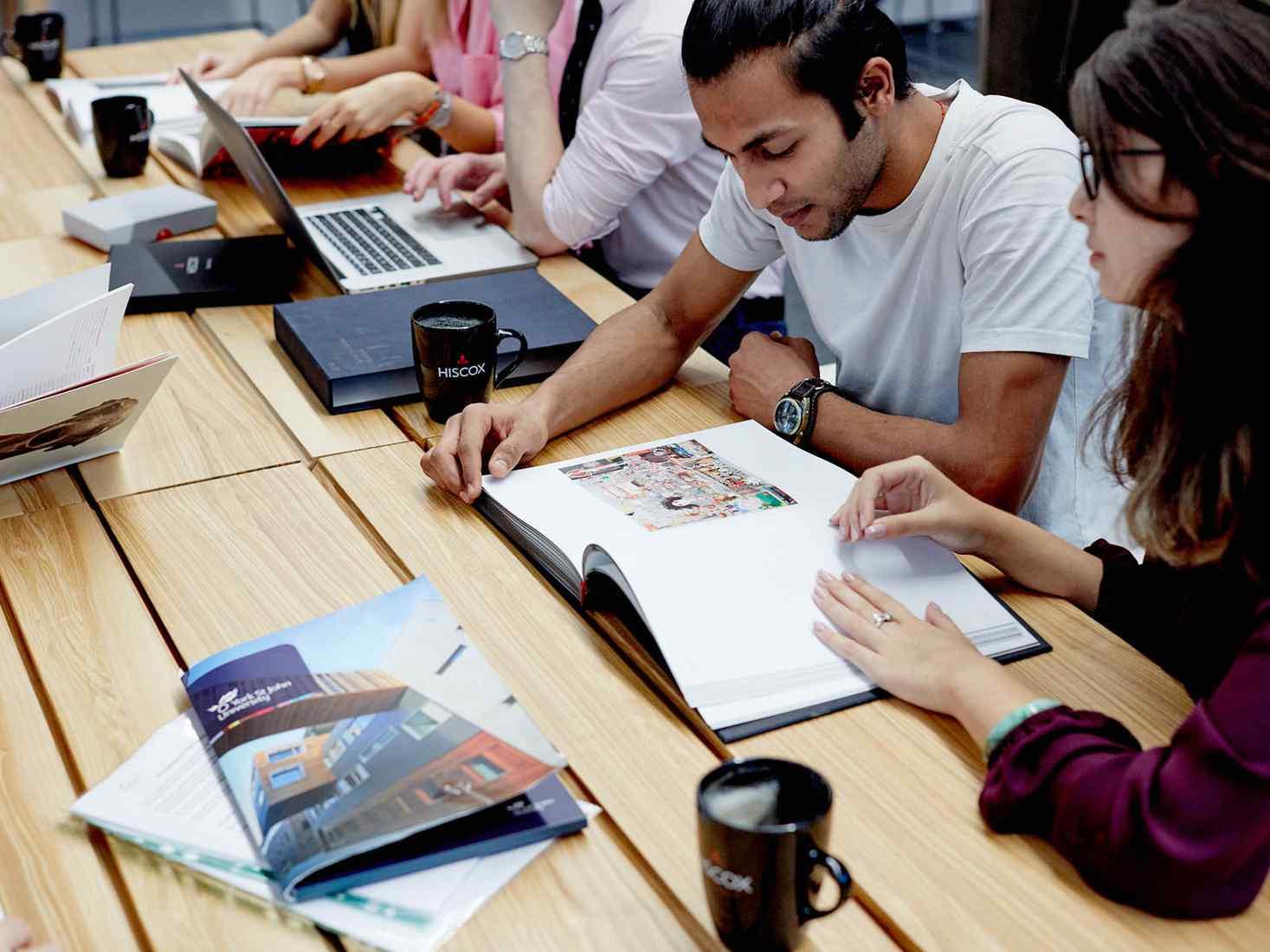 Students looking at book in seminar