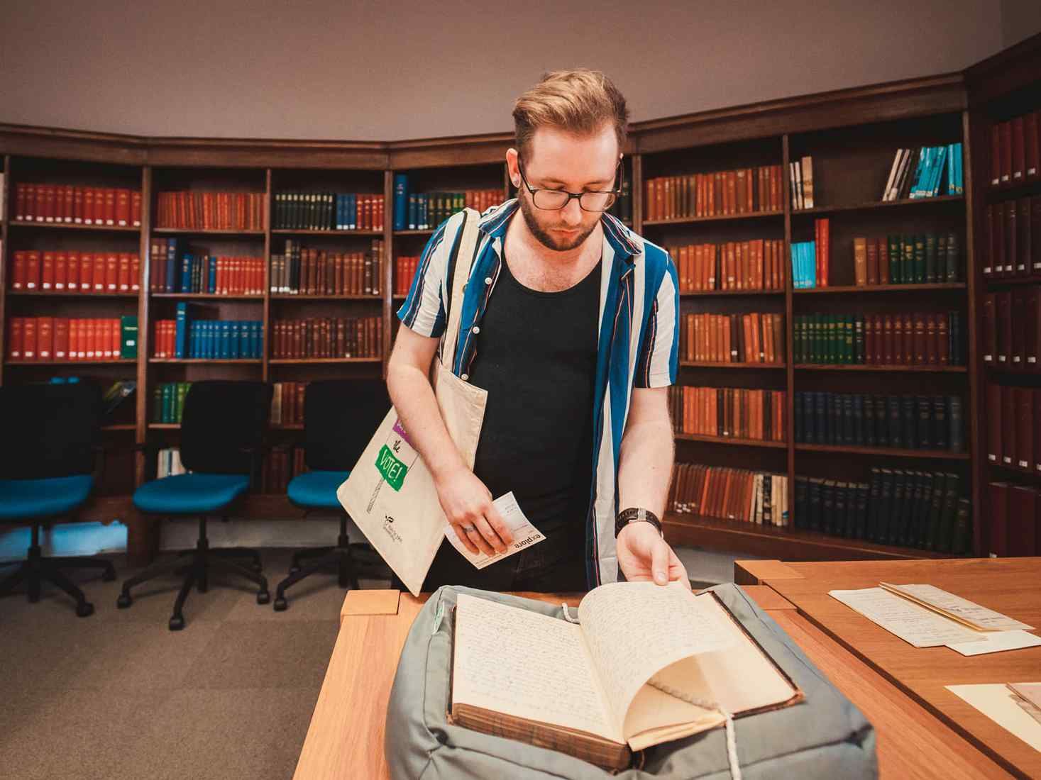 Student looking at historic book in library