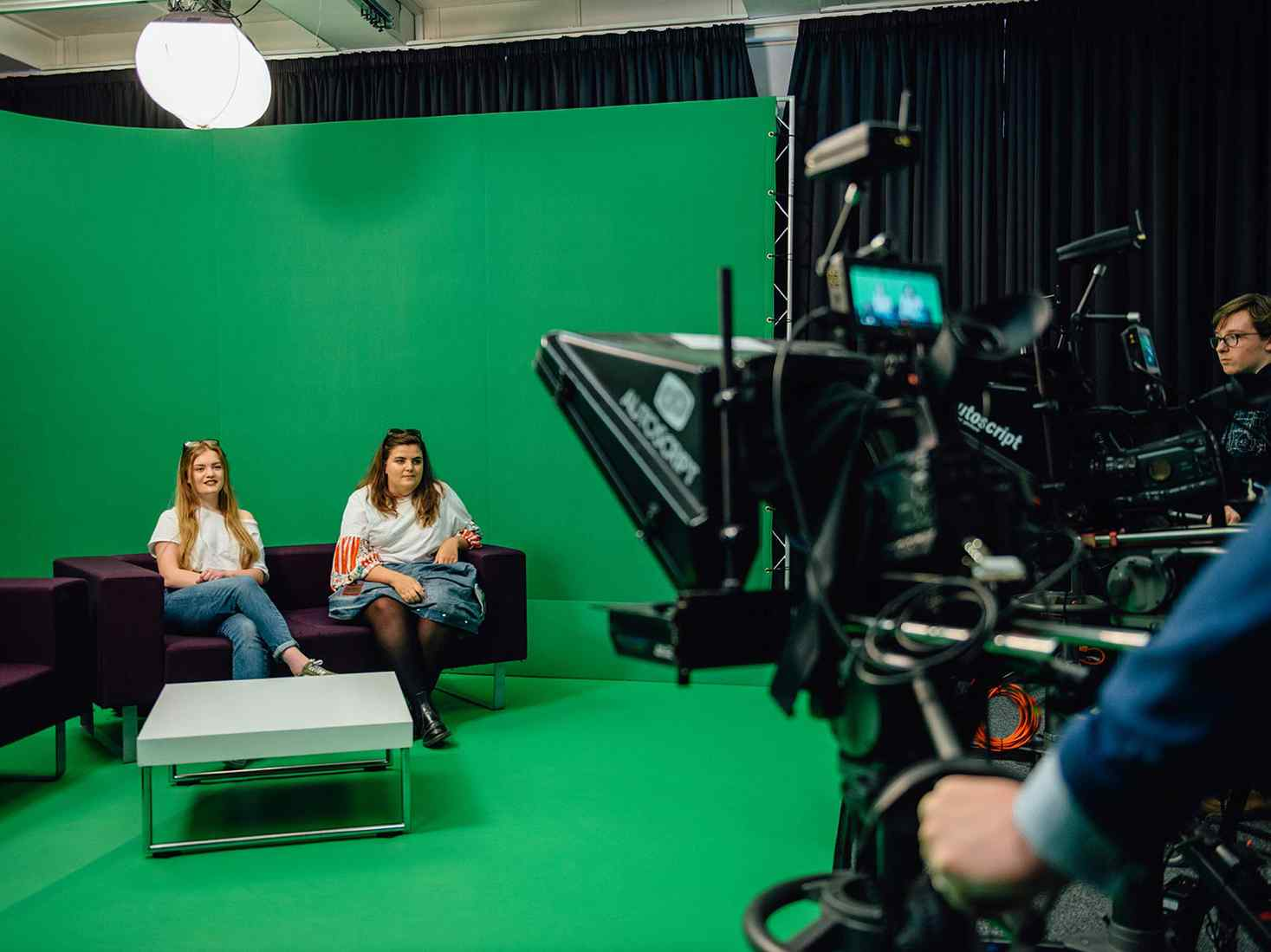 Two students sat in front of a green screen