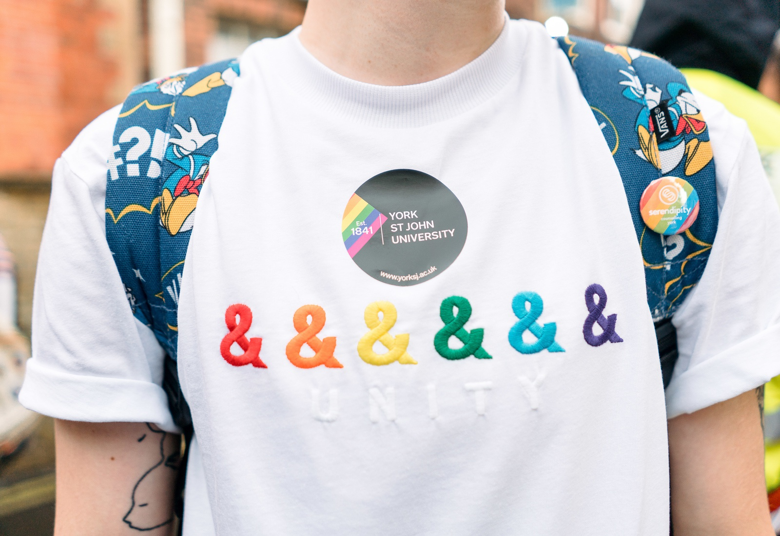 Close up of a Pride participant in a white T shirt with rainbow inclusive signs
