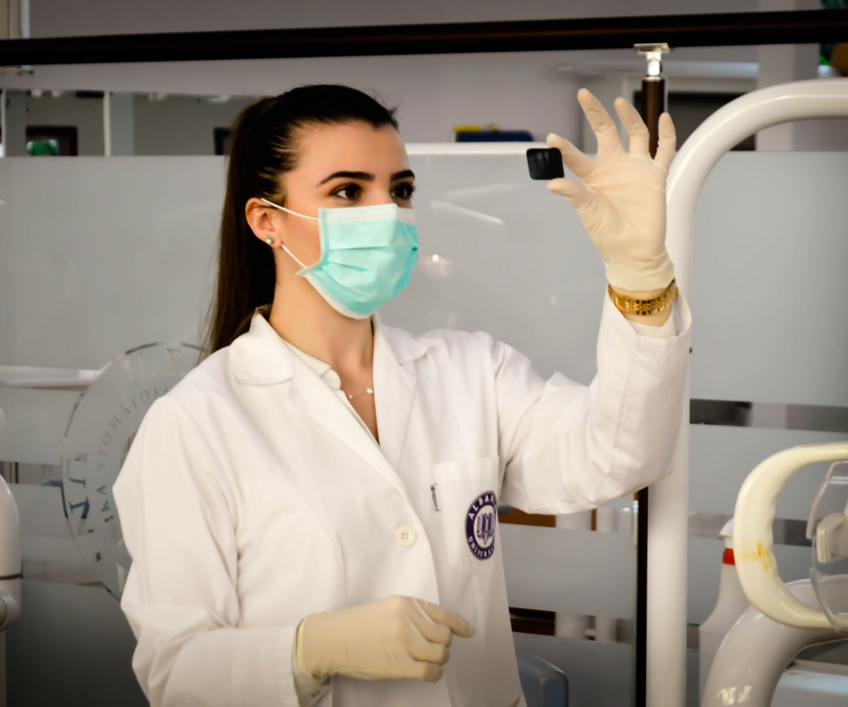 Woman in lab coat, gloves and face mask looking at slide