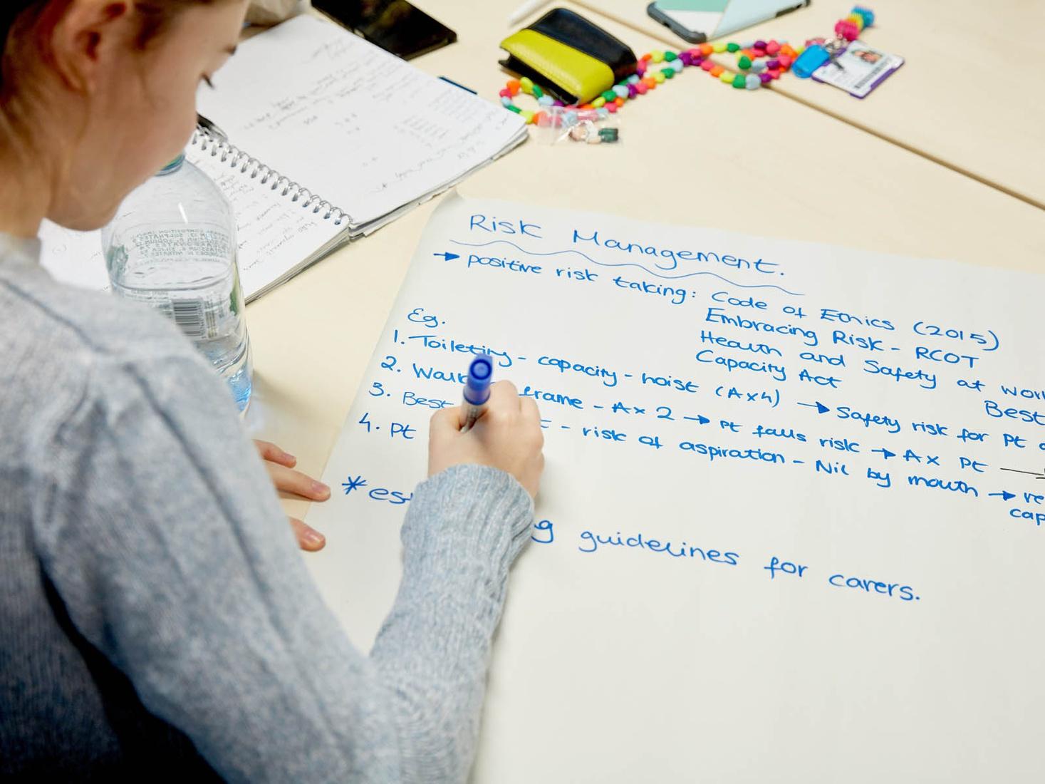 Student making notes on risk assessment