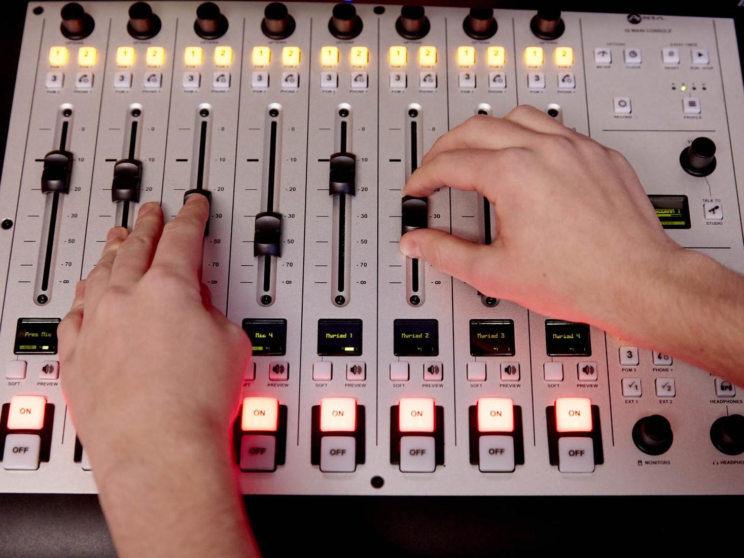Hands moving levels on recording desk
