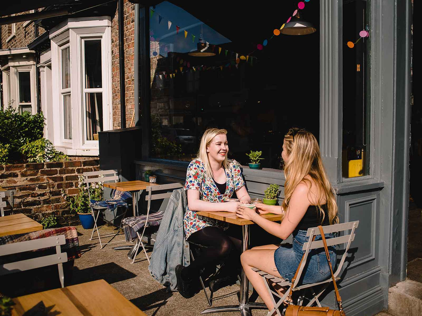 two students sat outside a cafe in the summer sun