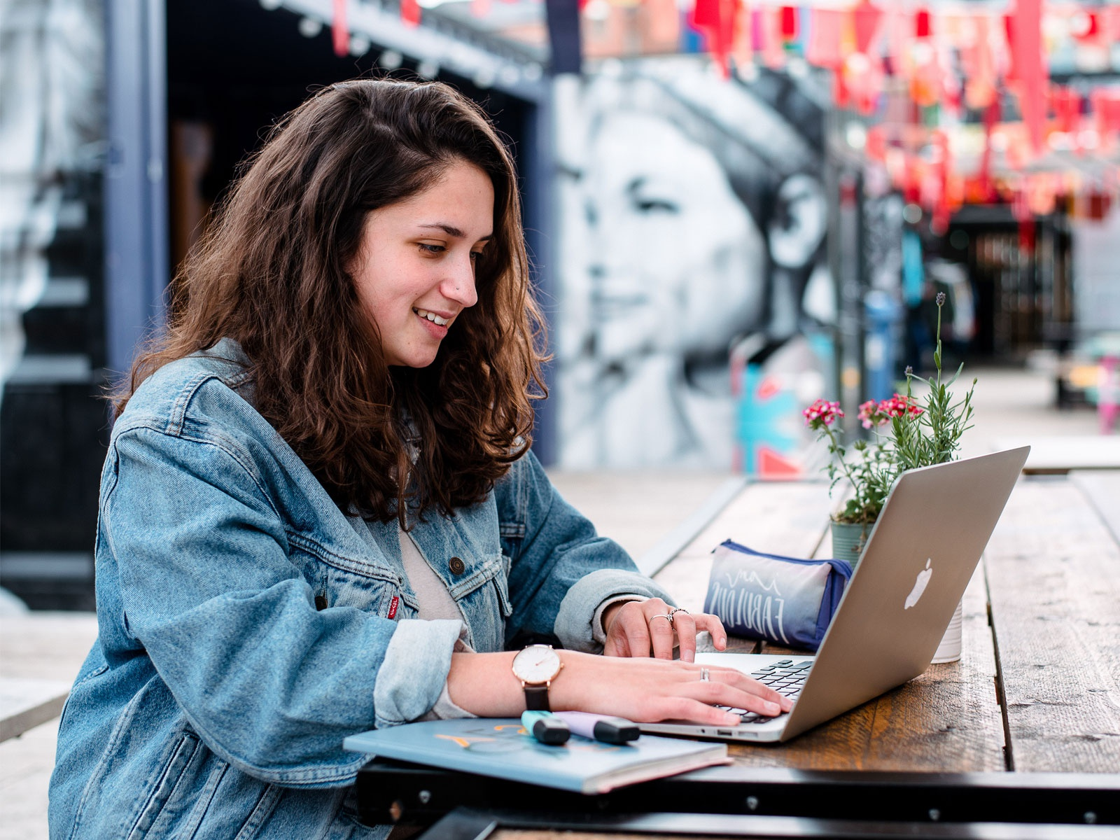 Female student, working on a laptop, in front of a mural at Spark York