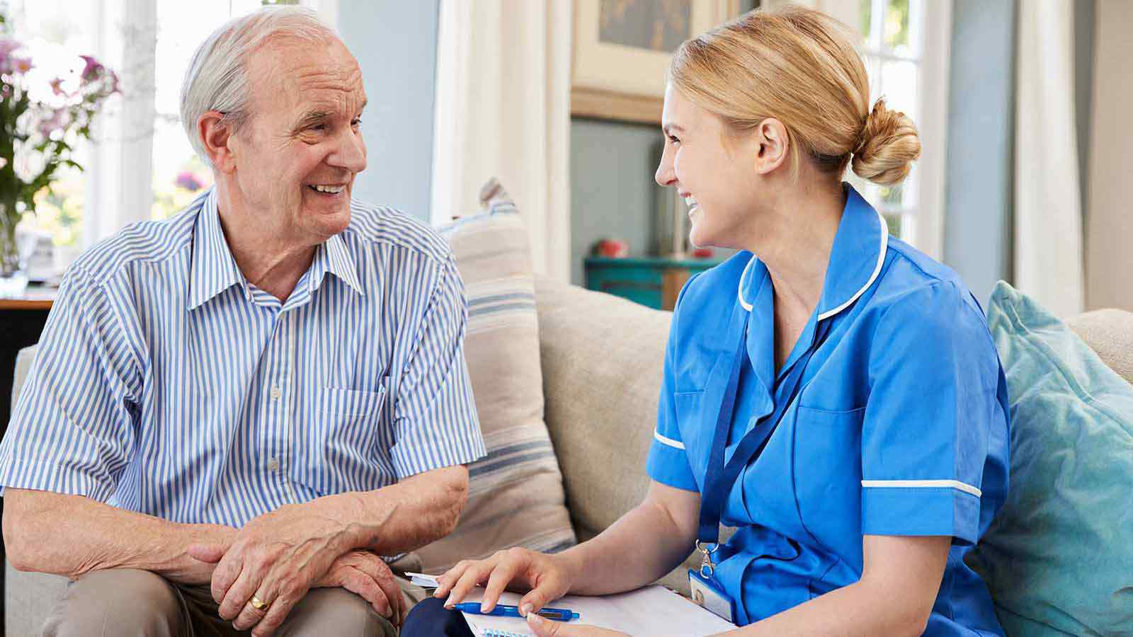 Nurse talking with patient on sofa