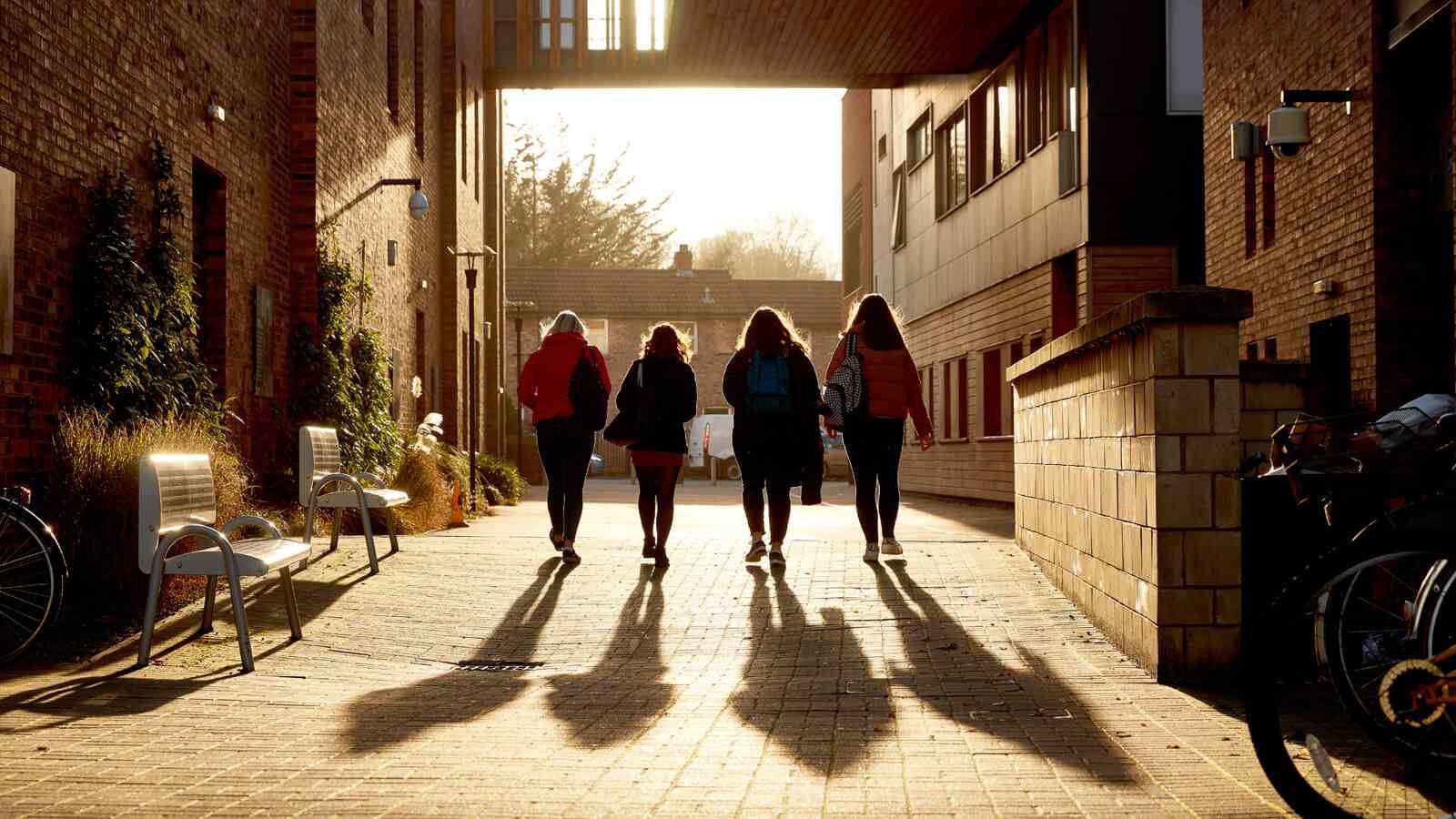 Students walking in sun outside De Grey building