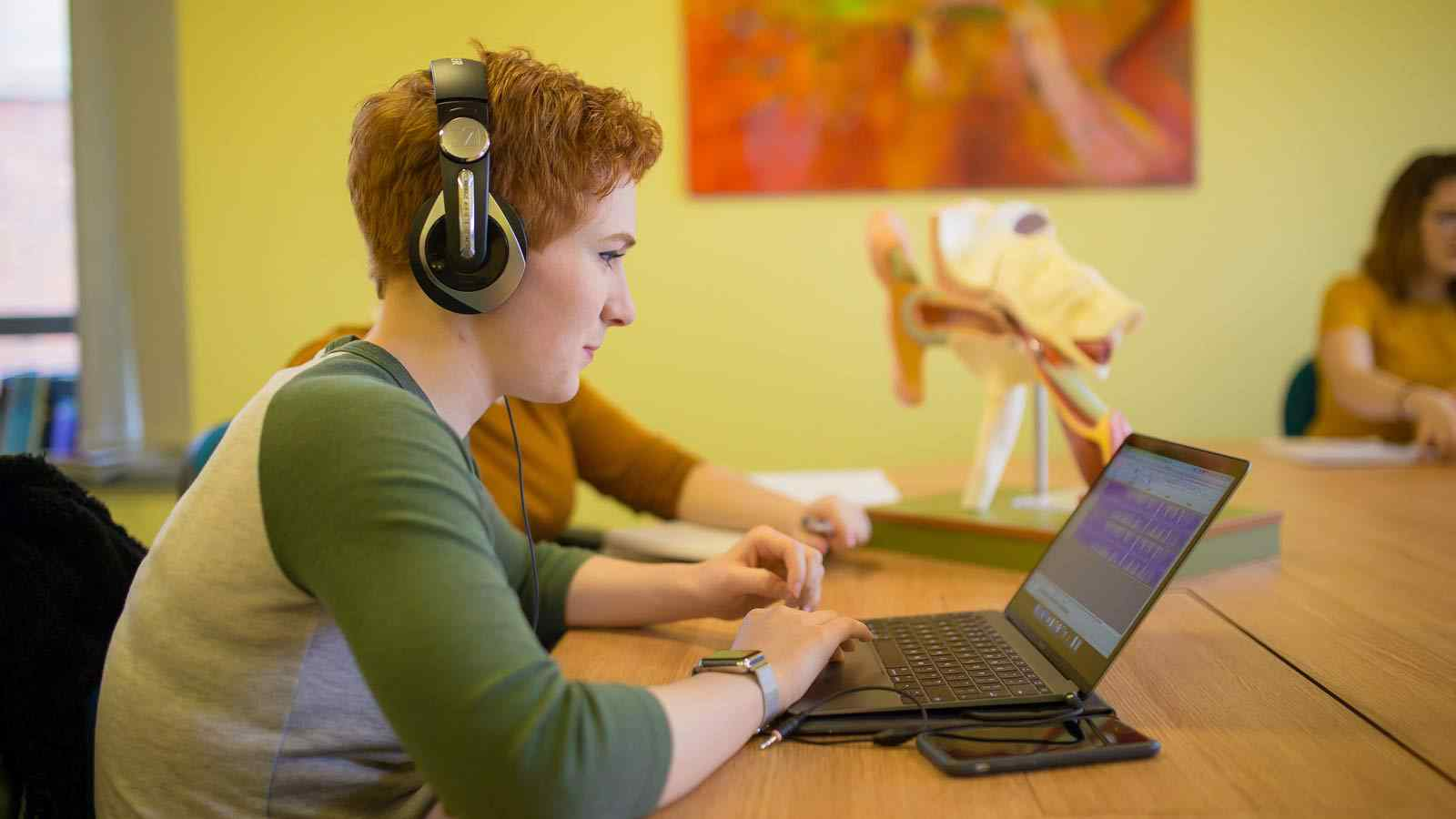 Student listening to sound file on laptop