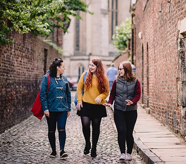 Three students walk down a cobbled lane in historic York