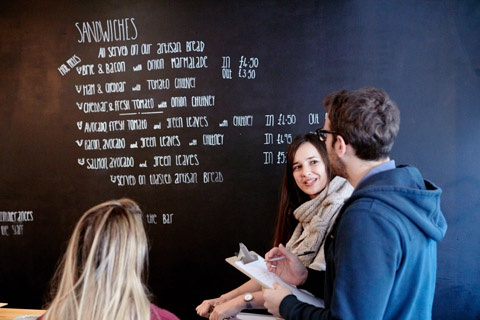 Business students in conversation with cafe owner