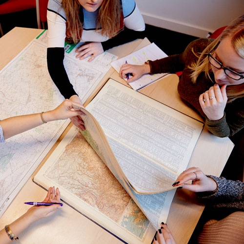 students looking at map on a desk