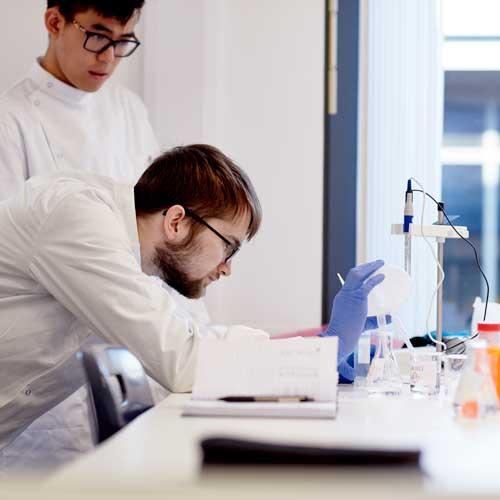 Biosciences students looking through microscope