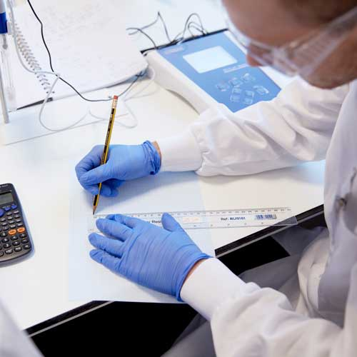 Biosciences student in laboratory drawing on graph paper and monitoring equipment