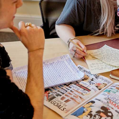Students taking notes and looking at magazine