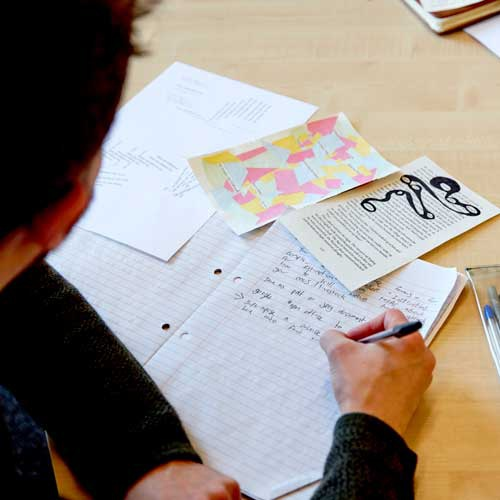 Student writing on paper, with creative writing activities for inspiration