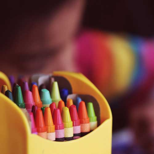 Crayons in packet, child in background drawing