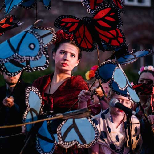 Performers holding butterfly puppets outside