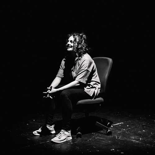 Drama performance, black and white image of student sat on chair on stage