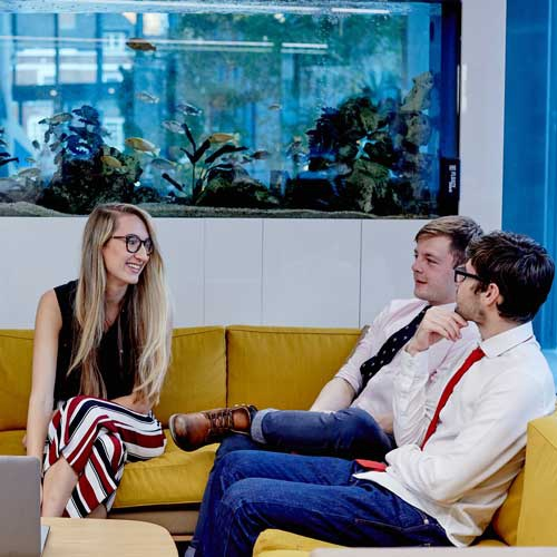 Students in business wear on sofas talking