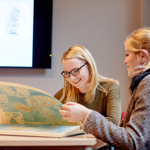 History students looking at map book
