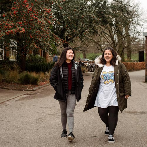 Two international students walking on campus