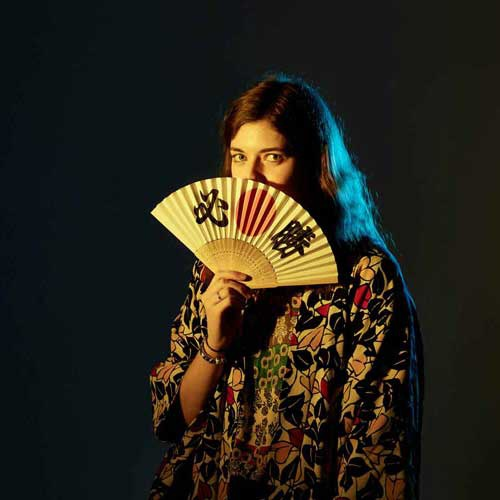 Student holding fan in front of face