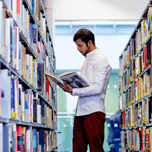 Student looking at book next to library shelves