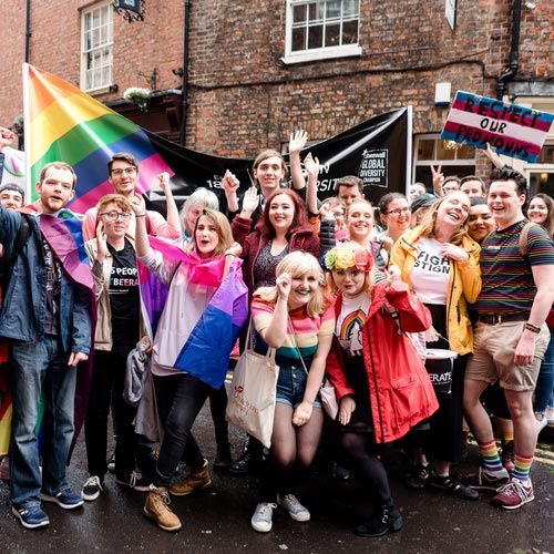A group of York St John students with a rainbow YSJ banner and wearing various pride flags, at the York Pride march.