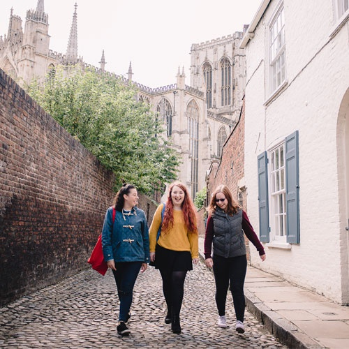 Three female students walking down a street with the Minster in the background.