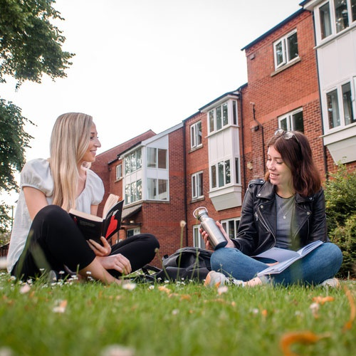 Two students chat on the grassy area outside the Grange accommodation.