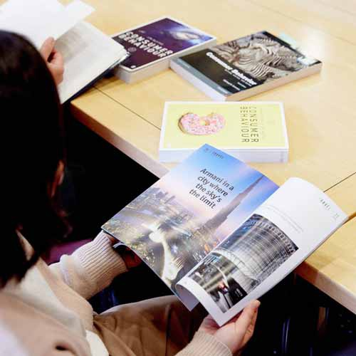 Student reading magazine with tourism advert