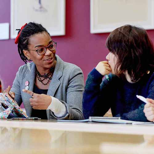 Two students discussing subject in seminar