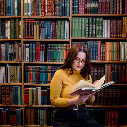 Student reading book in front of shelves in library